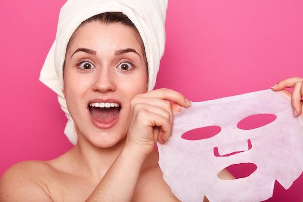 Headshot van verbaasd mooie jonge vrouw houdt cosmetische masker, voelt zich verfrist en energiek, heeft handdoek op het hoofd gewikkeld, kijkt met verbazing direct naar de camera, geïsoleerd over roze