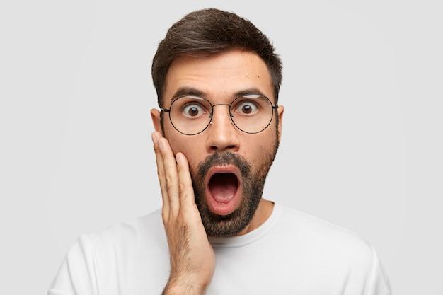Headshot van verbaasde bebaarde jonge blanke man staart met uitgestoken ogen, raakt wang met hand, mond wijd open, kan niet geloven in mislukking, poseert tegen witte muur