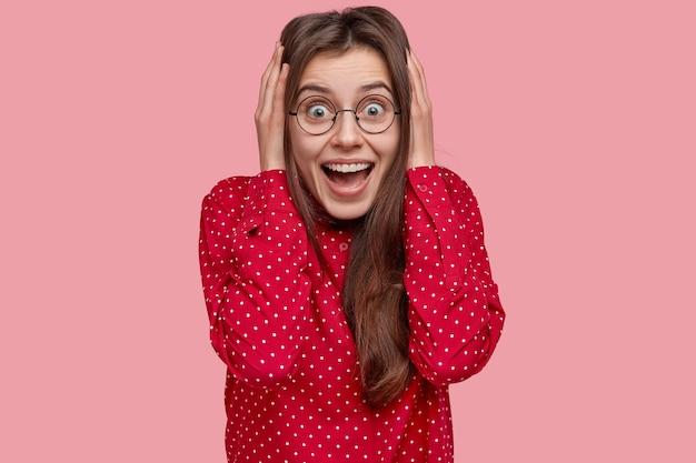 Headshot van verbaasde brunette vriendin staart met vreugdevolle uitdrukking, breed lacht, toont witte tanden, ontvangt voorstel