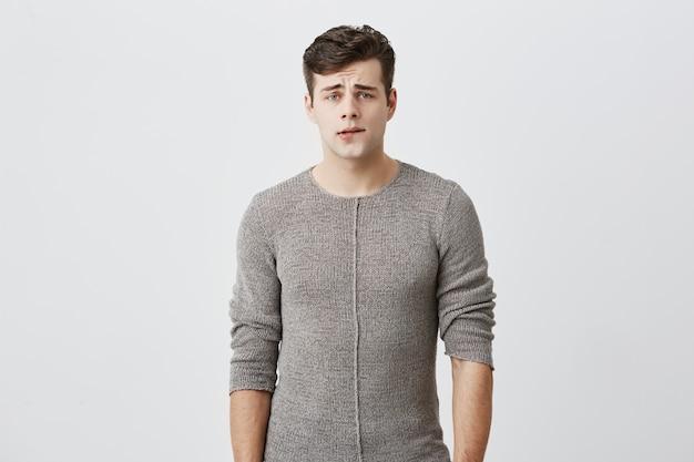 Headshot van verbaasde en verwarde mannelijke student, terloops gekleed, kijkend met zijn blauwe ogen, nadenkend over zijn volgende stap, niet wetend wat te doen. menselijk gevoel, emoties, gezichtsuitdrukkingen