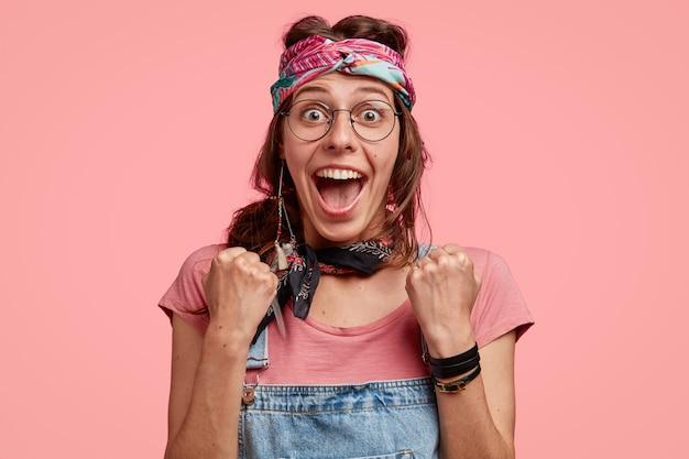 Headshot van verbaasde hippievrouw draagt stijlvolle outfit, balde vuisten van geluk