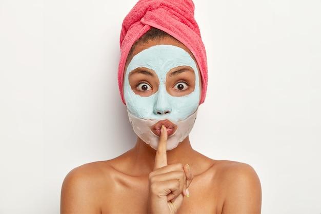 Headshot van verbaasde jonge vrouw maakt stil handteken, vertelt schoonheidsbehandeling, kijkt met afgeluisterde ogen, past gezichtsmasker van klei toe, siliconen pleister bij lippen, heeft mysterieuze uitdrukking, vertelt be qiet