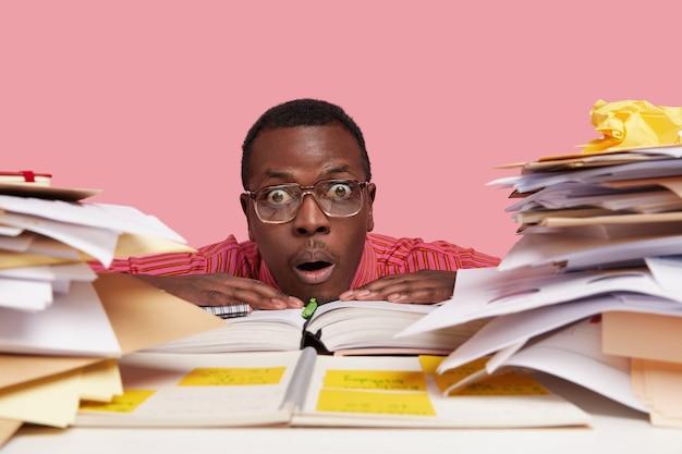 Headshot van verbijsterde mannelijke professor leunt hoofd op tafel, heeft gezichtsuitdrukking verrast, draagt een bril, houdt de handen op geopende notebook