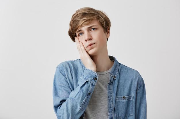 Headshot van verbijsterde overstuur jonge man draagt spijkerblouse houdt hand op wang en zegt: omg, daar ben ik moe van. geschokt blanke man beseft zijn schuld. negatieve gevoelens en emoties