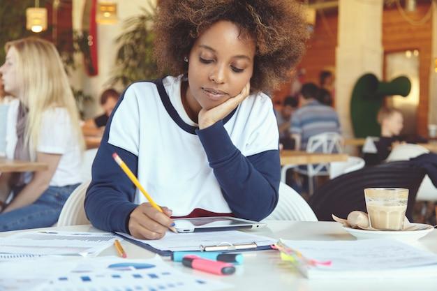 Headshot van vermoeide of verveelde afrikaanse student, die haar wang bij de hand legt tijdens het werken aan een diplomaproject, met een snelle internetverbinding op het touchpad, zittend in de cafetaria tijdens de lunchpauze