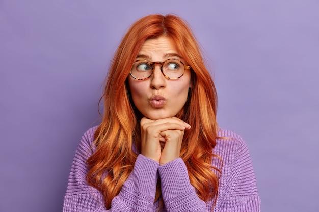 Headshot van verrast gember jonge vrouw houdt lippen gevouwen handen onder kin kijkt opzij gekleed in trui met lange mouwen.