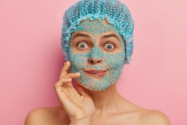 Headshot van verrast vrouw staat met zeezout scrub op gezicht, bijt lippen en staart met afgeluisterde ogen, voelt zich onder de indruk van iets, draagt een badmuts, verfijnt huidporiën, vermindert droogheid, donkere vlekken
