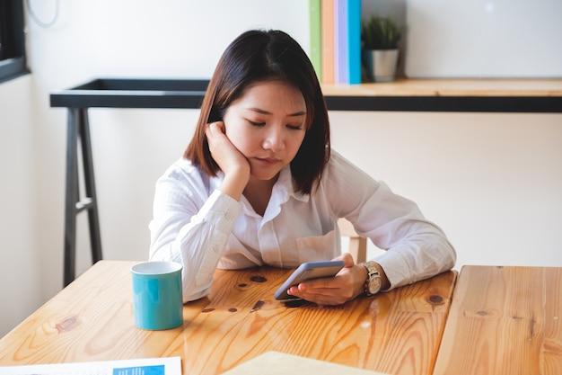 Headshot van verveelde vrouw in zakelijke casual gebruiken en kijken op slimme telefoon