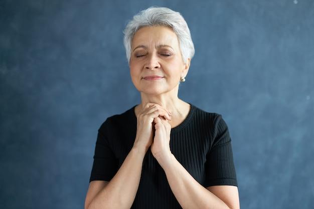 Headshot van vredige mooie rijpe vrouw met kort grijs haar poseren geïsoleerd met hoopvolle gezichtsuitdrukking, ogen gesloten houden, handen vastgehouden in gebed, hopend op het beste