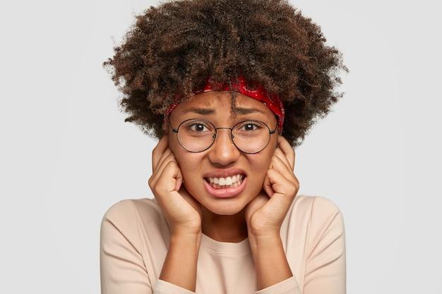 Headshot van vrij ontevreden vrouw sluit oren met wijsvingers, klemt tanden, fronst gezicht van ontevredenheid