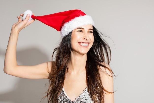 Headshot van vrolijk vrolijk donkerbruin langharig jong meisje in santahoed op grijze muur met copyspace