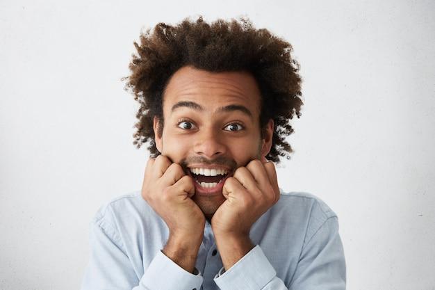 Headshot van vrolijke afro-amerikaanse mannelijke hand in hand onder kin dragen shirt