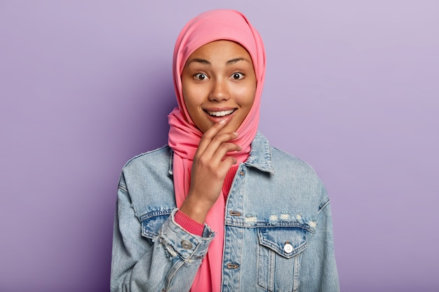 Headshot van vrolijke donkere moslimvrouw heeft een zachte glimlach, toont witte tanden, draagt roze hijab