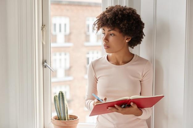 Headshot van vrouw draagt casual huishoudelijke kleding, schrijft informatie die ze zich herinnert in notitieblok, staan in de buurt van raam