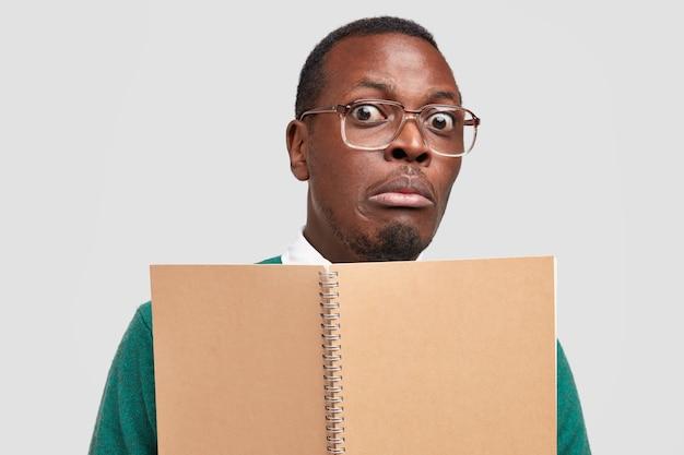 Headshot van zwarte nerd met bange uitdrukking, staart door bril, houdt bruin spiraalvormig notitieblok vast, kijkt verrassend naar camera