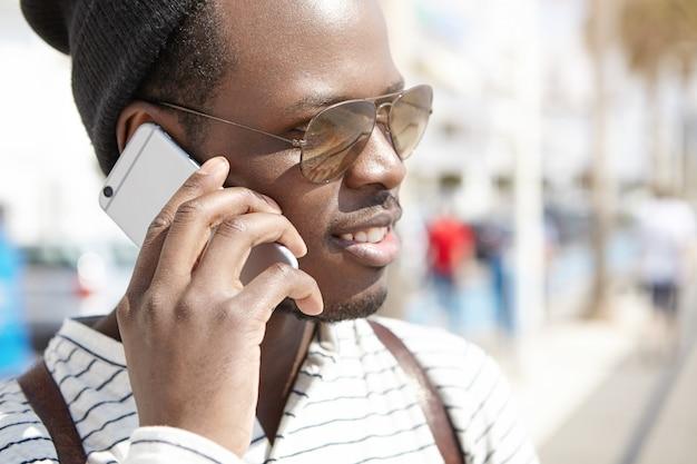 Headshot van zwarte persoon in schaduwen met telefoongesprek op zonnige lentedag, genieten van mooie wandeling door de straten van de badplaats. mensen op vakantie. jeugd en reizen. mens en techniek