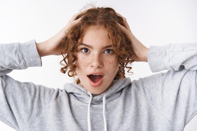 Headshot zorgeloos speels grappig aantrekkelijk roodharig jong 20s meisje met sproeten puistjes houden hand hoofd schreeuwen speels heimwee voelen dragen comfortabele grijze hoodie, staande vrolijke witte achtergrond