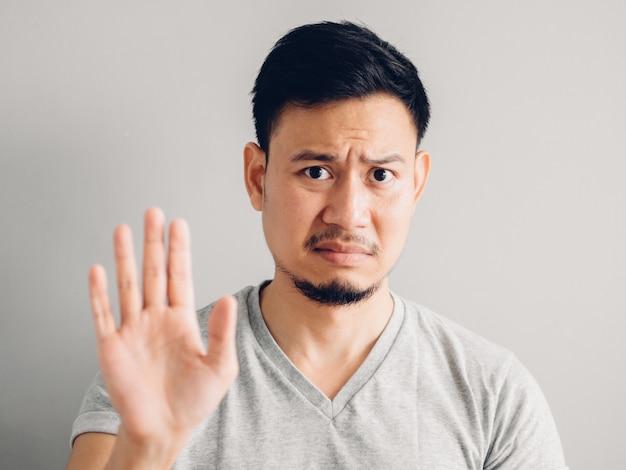 Headshotfoto van de aziatische mens met haat en smerig gezicht op grijze achtergrond.