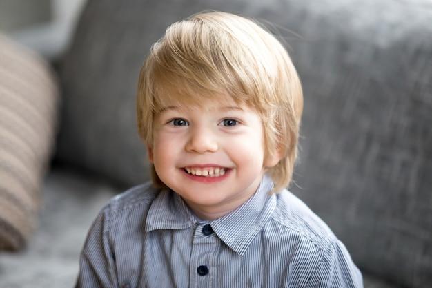 Headshotportret van leuke glimlachende jong geitjejongen die camera bekijken