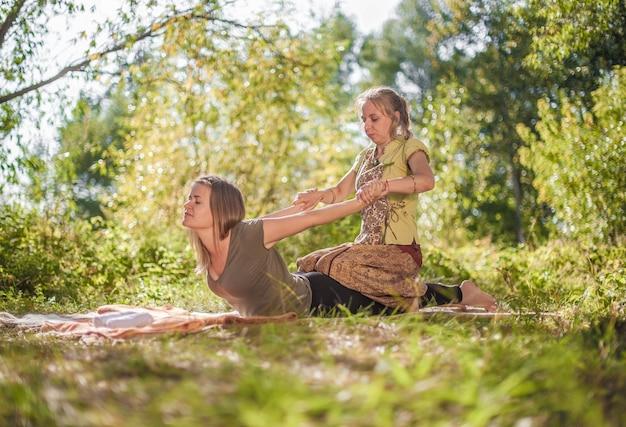 Healer geeft haar cliënt een verfrissende massage in het bos.