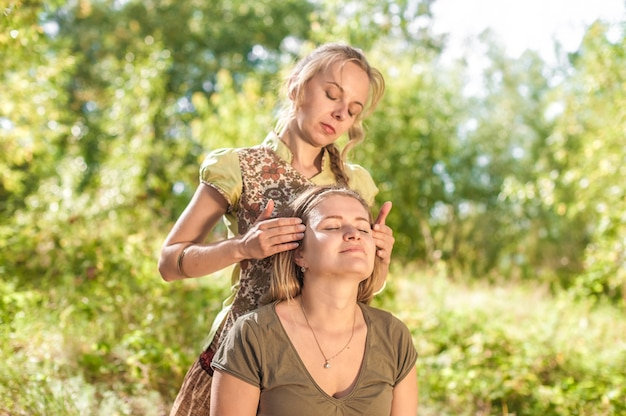 Healer geeft haar cliënt een verfrissende massage in het zonlicht