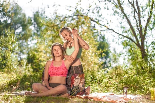 Healer geeft haar cliënt een verfrissende massage op de grond.