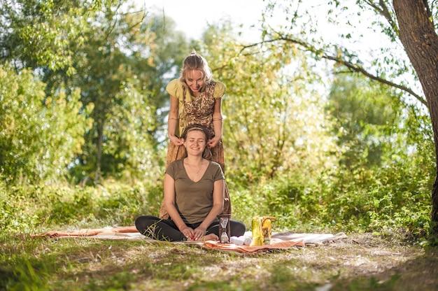 Healer past haar massagevaardigheden toe op haar cliënt op het gras.