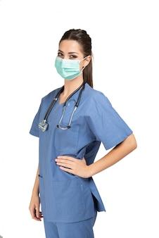 Healtcare arbeider met stethoscoop die op wit wordt geïsoleerd dat een masker draagt