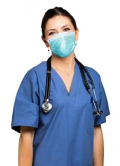 Healtcare arbeider met stethoscoop op wit wordt geïsoleerd dat een masker, coronavirus concept draagt dat