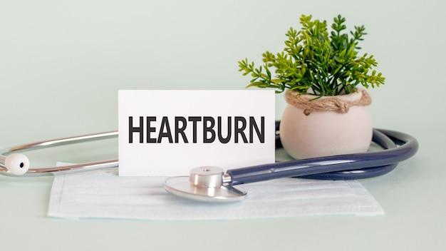 Heartburn woorden geschreven op witte medische kaart, met medicijnmasker, stethoscoop en groene bloem op muur