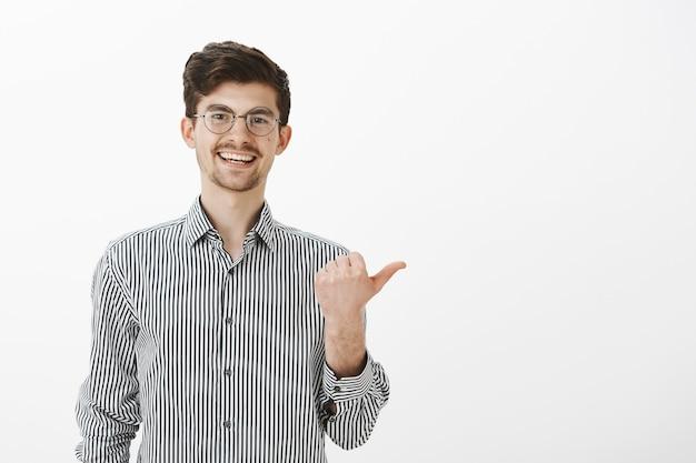 Heb je gehoord wat de man zei? portret van zorgeloze vriendelijke mannelijke collega met snor en baard, naar rechts wijzend met duim en breed glimlachend, wijzend op persoon en roddelen over hem