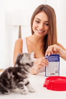 Heb je honger? mooie jonge vrouw die een pakje met kattenvoer opent en glimlacht terwijl een klein katje wacht terwijl ze op de voorgrond zit