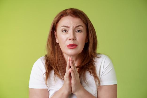 Heb zo snel mogelijk hulp nodig tedere timide roodharige vrouw van middelbare leeftijd pleiten druk op de handpalmen tegen elkaar bidden smeken hoopvol oprecht kijken camera smeken vriend gunst staan groen muur dwaas