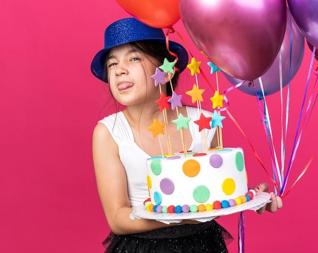Hebzuchtig jong kaukasisch meisje met blauwe feestmuts steekt tong uit met verjaardagstaart en heliumballonnen geïsoleerd op roze muur met kopieerruimte