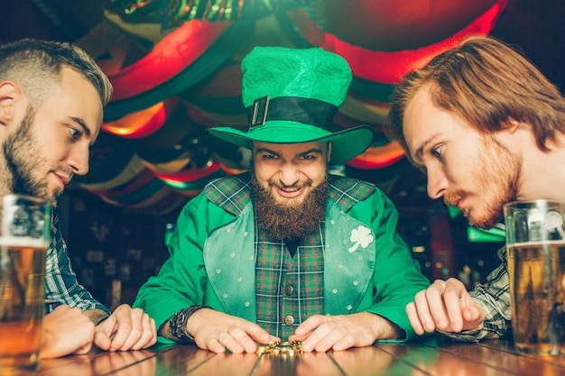 Hebzuchtige jonge man in groen pak zit aan tafel met vrienden en kijkt naar gouden munten die hij pakte. andere jongens kijken ook naar hen. mokken bier staan op tafel.
