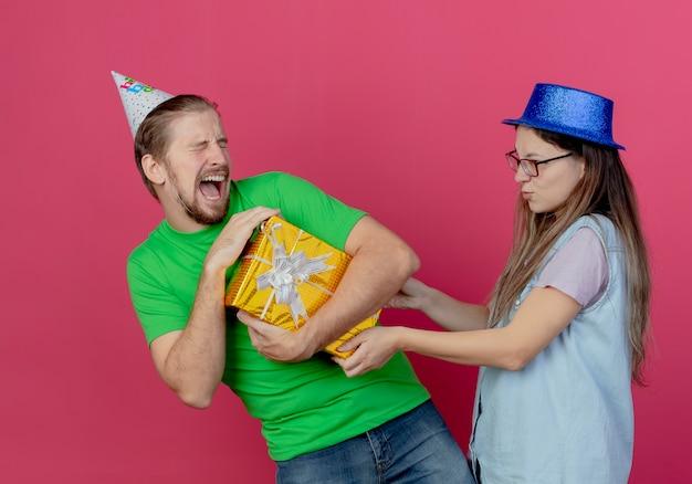 Hebzuchtige jonge man met feestmuts houdt geschenkdoos en onaangenaam jong meisje met blauwe feestmuts houdt doos geïsoleerd op roze muur