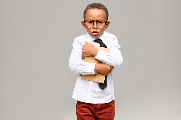 Hebzuchtige nerdy donkere huidskleurige basisschoolleerling die schooluniform en bril draagt die strak schrift vasthoudt en roept. jeugd, onderwijs, leren en levensstijlconcept