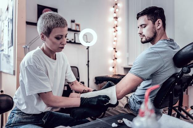 Hecht dichterbij. attente, geconcentreerde tattoo-meester die een papieren handdoek gebruikt om extra nattigheid van het oppervlak te absorberen