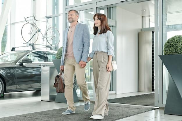 Hedendaags gelukkig jong stel in vrijetijdskleding hand in hand terwijl ze een groot autocentrum binnengaan terwijl ze een nieuwe auto gaan kiezen en kopen