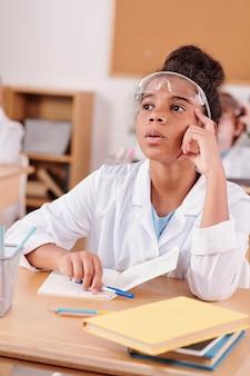 Hedendaags schoolmeisje van afrikaanse etniciteit die tijdens het experiment aandachtig luistert naar de scheikundeleraar terwijl ze op klasgenoten zit