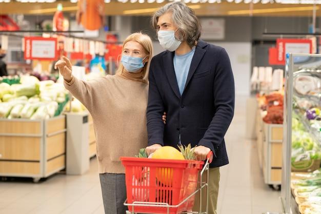 Hedendaags volwassen stel in vrijetijdskleding en beschermende maskers die langs de grote supermarkt bewegen terwijl de vrouw naar een van de afdelingen wijst