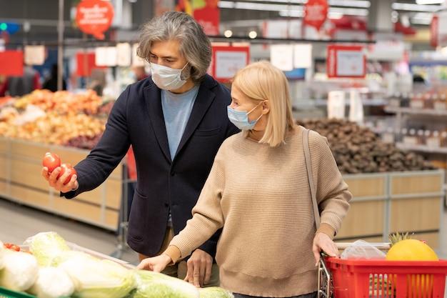 Hedendaags volwassen stel in vrijetijdskleding en beschermende maskers die verse rijpe groenten in de supermarkt kiezen terwijl ze bij een groot display staan