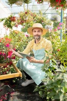 Hedendaagse boer in werkkleding die naar je kijkt terwijl hij op zoek is naar namen van nieuwe soorten bloemen in de kas