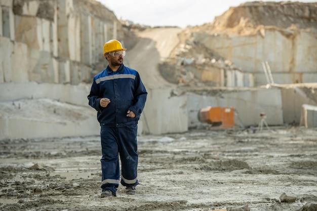 Hedendaagse bouwer in uniform naar beneden bewegende bouwplaats