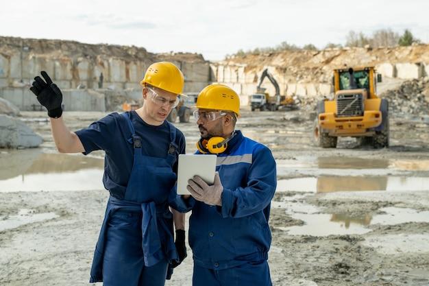 Hedendaagse bouwers bespreken schets in tablet tijdens het werk