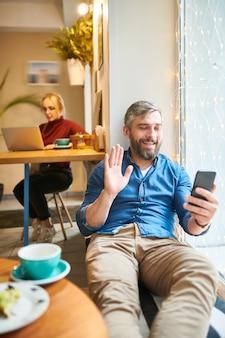 Hedendaagse casual bebaarde man zwaait met zijn hand terwijl hij praat via videochat in smartphone terwijl hij ontspant in een café