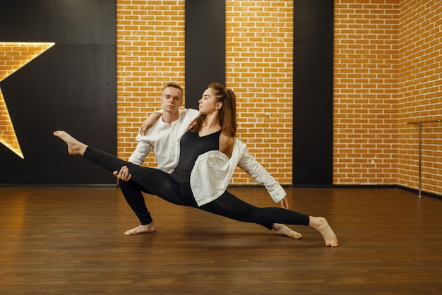 Hedendaagse dansartiesten, paar poseren in studio. mannelijke en vrouwelijke dansers op training in de klas, moderne dans, rekoefeningen
