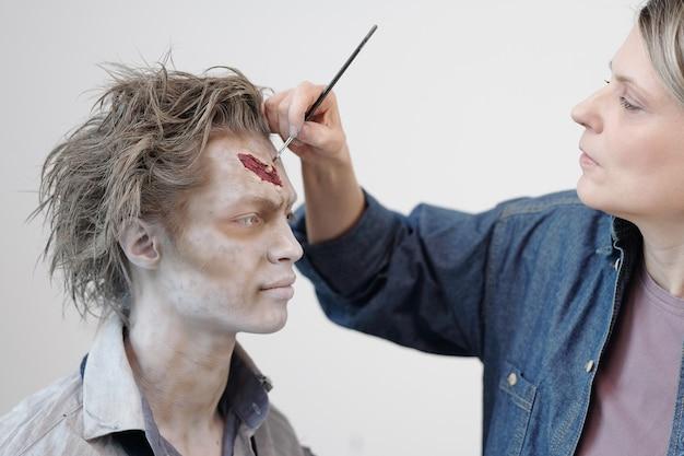 Hedendaagse gelaatskunstenaar met borstel die zombiemake-up toepast op het gezicht van een jonge zakenman of acteur tegen een witte muur in kantoor of studio