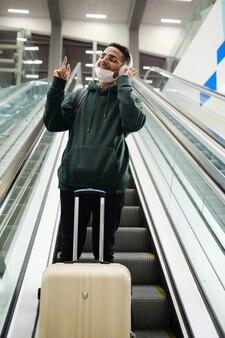 Hedendaagse gelukkige jonge man in vrijetijdskleding die geniet van zijn favoriete muziek in een koptelefoon terwijl hij op de trap van de bewegende roltrap op de luchthaven staat
