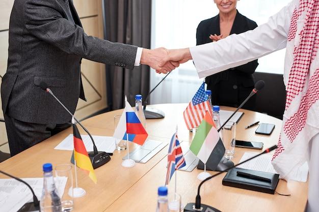 Hedendaagse interculturele afgevaardigden schudden elkaar de hand na een succesvolle vergadering persconferentie met microfoons, in directiekantoor. kaukasische en arabische leidinggevenden ondertekenden een bilaterale overeenkomst